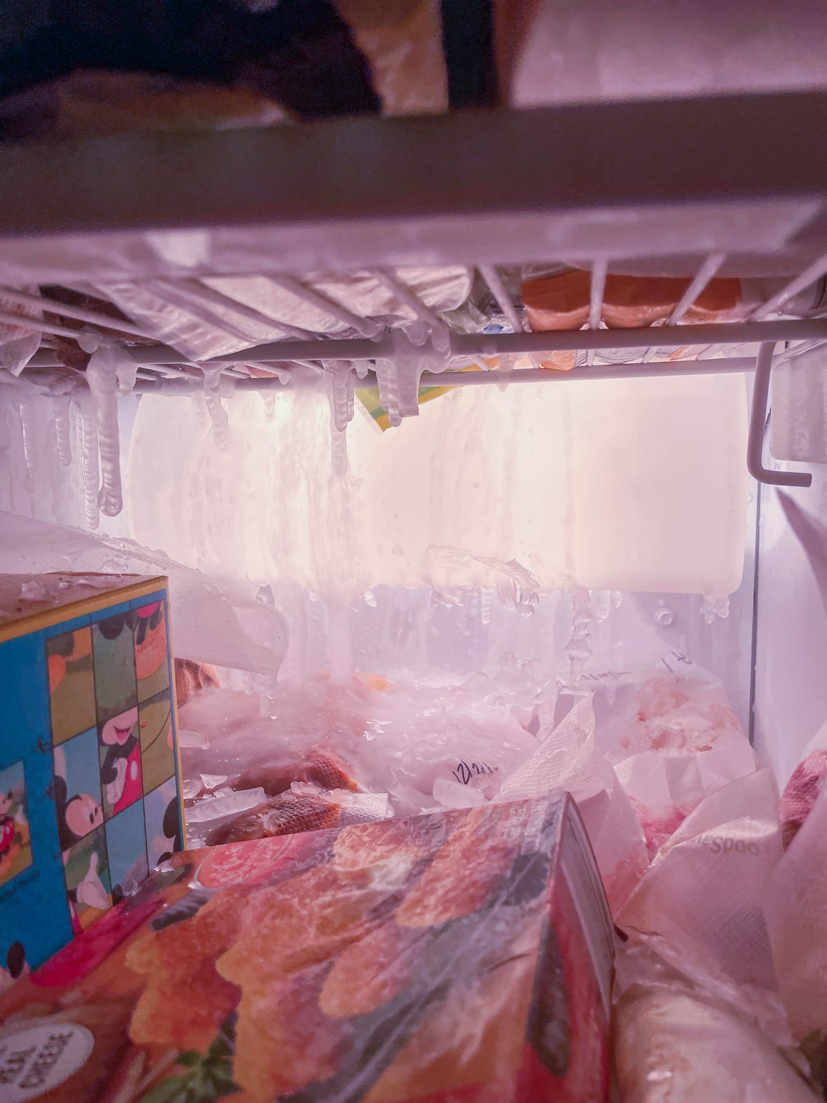 Inside of a freezer with icicles hanging down over frozen food.